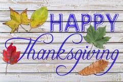 Acción de gracias feliz con varios hoja del otoño escrita en la madera blanca Fotos de archivo libres de regalías