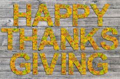 Acción de gracias feliz escrita en el tablero de madera con las palabras hechas de hojas Imagen de archivo