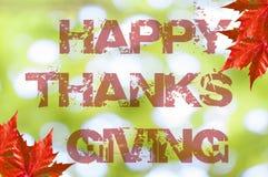 Acción de gracias feliz escrita en fondo del bokeh con la hoja roja Imágenes de archivo libres de regalías