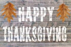 Acción de gracias feliz escrita en fondo del tablero de madera con dos hojas Imagen de archivo