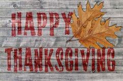 Acción de gracias feliz roja escrita en fondo del tablero de madera con dos hojas Fotografía de archivo