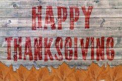 Acción de gracias feliz roja escrita en fondo del tablero de madera con la hoja Fotografía de archivo libre de regalías