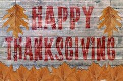 Acción de gracias feliz roja escrita en fondo del tablero de madera con la hoja Foto de archivo libre de regalías