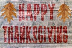 Acción de gracias feliz roja escrita en fondo del tablero de madera con la hoja dos Fotografía de archivo