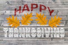 Acción de gracias feliz roja escrita en fondo del tablero de madera con las hojas amarillas Fotografía de archivo libre de regalías