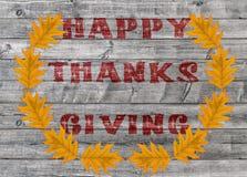 Acción de gracias feliz roja escrita en fondo del tablero de madera con las hojas amarillas Foto de archivo