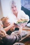 Acción de gracias: La abuela pasa habas y el relleno a través de la tabla Fotografía de archivo libre de regalías