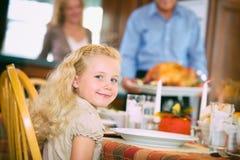 Acción de gracias: La muchacha sonriente espera pacientemente la cena de Turquía Foto de archivo