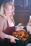 Acción de gracias: Womanr que sostiene Turquía en la asación de Pan After Taking Foto de archivo libre de regalías