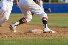 Acción del béisbol - los pies primero resbalan dentro de base Foto de archivo libre de regalías