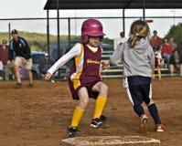Acción del beísbol con pelota blanda de las muchachas en la primera base Fotos de archivo