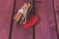 Acción del canela con el corazón en tablones de madera Imagen de archivo