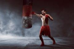 Acción del entrenamiento asiático del hombre del boxeador con el saco de arena Imagenes de archivo