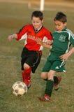 Acción del juego de fútbol de los muchachos Imagenes de archivo