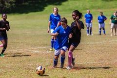 Acción del juego del desafío de la muchacha del fútbol del fútbol Fotografía de archivo