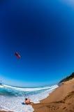 Acción del lanzamiento de la playa de la cometa que practica surf   Imágenes de archivo libres de regalías