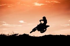 Acción del motocrós con el fondo de la puesta del sol Foto de archivo