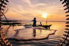 Acción del pescador al pescar en la puesta del sol Fotos de archivo