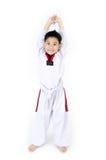Acción del Taekwondo de un muchacho asiático de la sonrisa Imágenes de archivo libres de regalías
