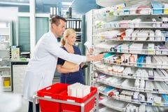 Acción feliz de And Assistant Counting del farmacéutico adentro Foto de archivo