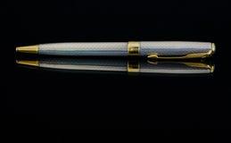 Acción - plata y oro Pen Against una superficie reflexiva negra Imagenes de archivo