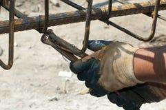 Acciaio di rinforzo dei legami dell'operaio di costruzione Fotografia Stock