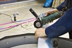 Acciaio di taglio del lavoratore con la smerigliatrice elettrica della ruota Immagini Stock
