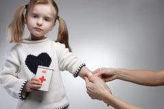 Accident. Parent applying band aid to sad child Stock Photos