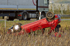 Accident. The wreck of a car, upside down beside a motorway (freeway, autoroute, autobahn) with a lorry passing Stock Images