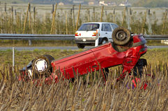 Accident. The wreck of a car, upside down beside a motorway (autoroute, freeway, autobahn Stock Photos