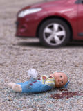 Accident. Closeup of a broken doll and bleeding on the asphalt and broken glass of a vehicle Stock Photo