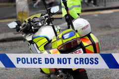 Accident or crime scene. Policeman and police motorcycle behind cordon tape at an accident or crime scene Stock Photos