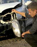 Accident Damage. A man inspecting damage to a car Stock Photography