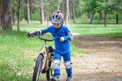 Accident de bicyclette Badine le concept de sécurité Garçon transportant son vélo pour réparer l'endroit photographie stock libre de droits