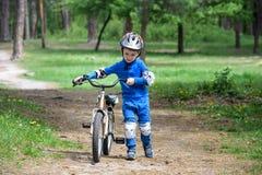 Accident de bicyclette Badine le concept de sécurité Garçon transportant son vélo pour réparer l'endroit Images stock