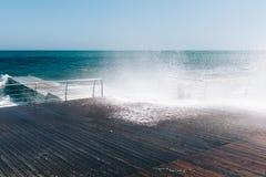 Accident de vagues contre la promenade images stock