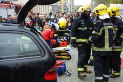 Accident demonstration scenery by firebrigade. A injured person removed from interior of crash car with security equipement and firefighters straped her with Stock Image