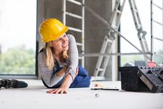 An accident of a woman worker at the construction site. royalty free stock image