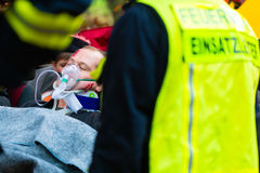 Accident - Fire brigade, Victim with respirator. Accident - Fire brigade and Rescue team pulling cart with wounded person wearing a neck brace and respirator Royalty Free Stock Image