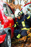 Accident - Fire brigade rescues Victim of a car. Accident - Fire brigade rescues accident Victim of a car, firefighter holds a drip for Infusion Stock Photo