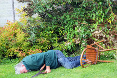 Accident, garden fall over. Danger. man unconscious. A Senior man has fallen off a chair he was standing on. He has a pair of sharp shears in his hand. He is Royalty Free Stock Image