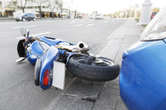 Accident motorcycle and cars on  road. The accident blue bike with a blue car. The motorcycle crashed into the bumper of the car on the road. The motorcycle lies Royalty Free Stock Photo