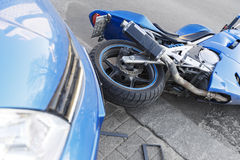 Accident motorcycle and cars on  road. The accident blue bike with a blue car. The motorcycle crashed into the bumper of the car on the road. The motorcycle lies Royalty Free Stock Images