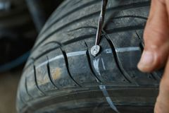 Accident with punctured tires concept. Solve problem wheel in garage auto repair shop service. replacement repairman fixing car`s tire trying to remove nail royalty free stock image