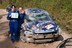 After accident in Rally St. Petersburg 2011. Pilot Denis Nikilaev with assistant after accident and his crash Chery car Royalty Free Stock Photos
