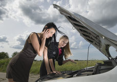 Accident on a road. Two young women with broken down car Stock Photos