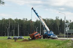 A boom truck hooking and lifting an overturned lorry, Moscow suburbs, Russia. Stock Photo