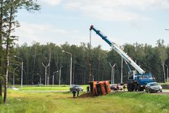 A boom truck hooking and lifting an overturned lorry, Moscow suburbs, Russia. Stock Image