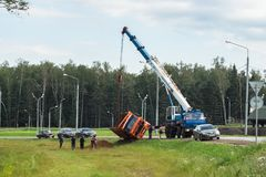 A boom truck hooking and lifting an overturned lorry, Moscow suburbs, Russia. Royalty Free Stock Photos