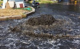 Accident sewerage system. Water flows over the road from sewer. Accident in sewer. Breakthrough sewerage system. Water flows out o. F manhole. Having poured stock photo